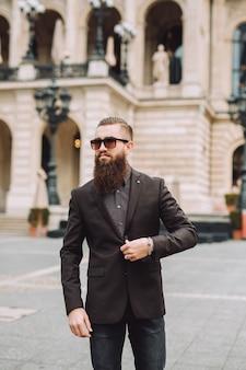 Junger mann mit langem bart auf der stadtstraße.