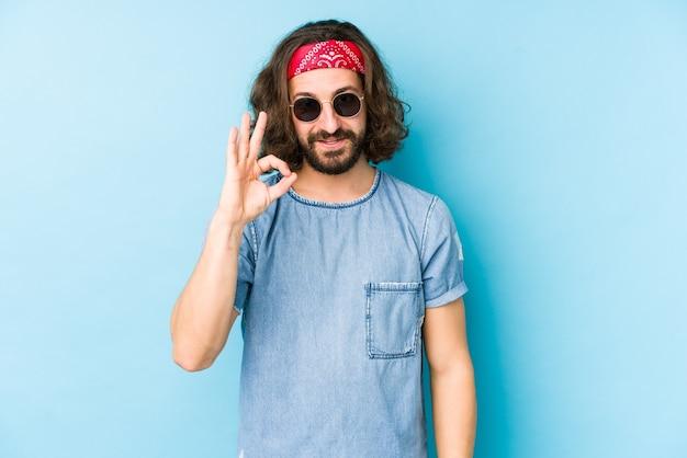 Junger mann mit langen haaren, der einen festival-hipster trägt, sieht isoliert fröhlich und zuversichtlich aus und zeigt ok geste.