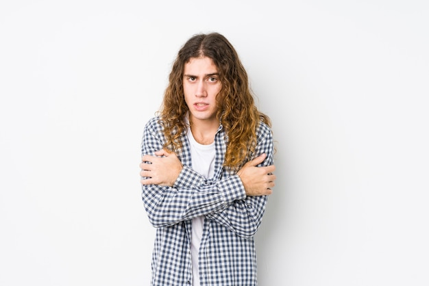 Junger mann mit langen haaren, der isoliert aufgrund einer niedrigen temperatur oder einer krankheit kalt wird.