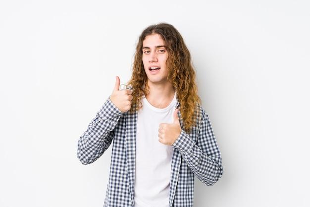Junger mann mit langen haaren, der isoliert posiert und beide daumen hochhebt, lächelnd und selbstbewusst.