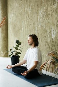 Junger mann mit langen haaren, die auf yogamatte meditieren, achtsamkeitskonzentration zu hause, entspannende und ruhige praxis