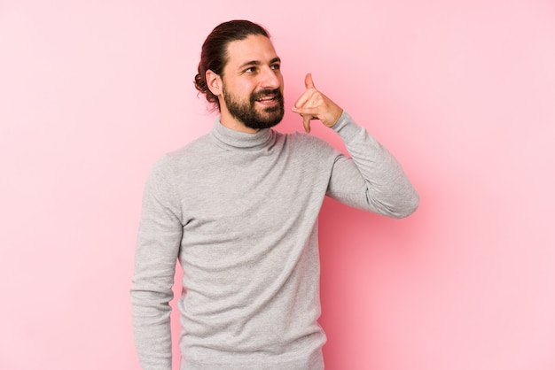 Junger mann mit langen haaren, isoliert auf einem rosa, das eine handy-anrufgeste mit den fingern zeigt.