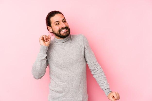 Junger mann mit langen haaren, isoliert auf einem rosa raum, der tanzt und spaß hat.