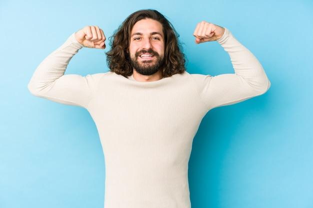 Junger mann mit langen haaren, isoliert auf einer blauen wand, die kraftgeste mit armen zeigt, symbol der weiblichen macht