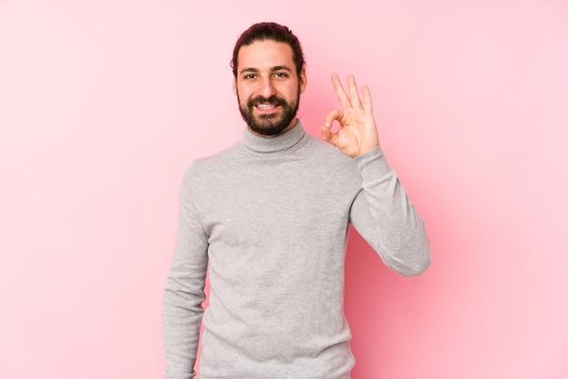 Junger mann mit langen haaren isoliert auf einer rosa fröhlichen und selbstbewussten geste, die ok zeigt.