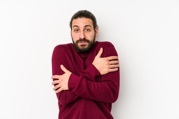 Junger mann mit langen haaren, isoliert auf weiß, der wegen niedriger temperatur oder einer krankheit kalt wird.