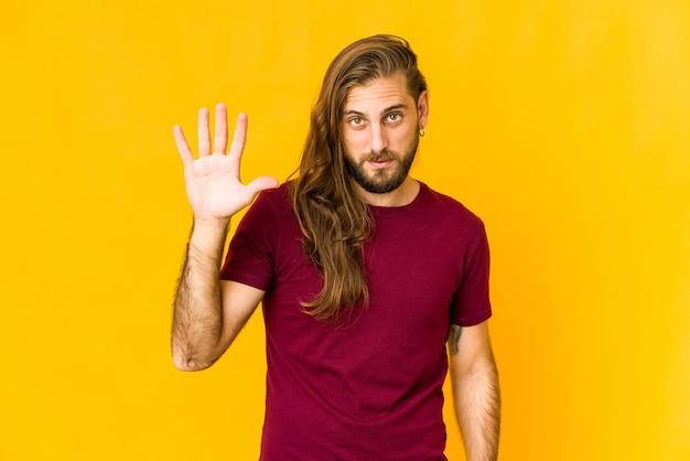 Junger mann mit langen haaren sieht fröhlich lächelnd aus und zeigt nummer fünf mit den fingern.