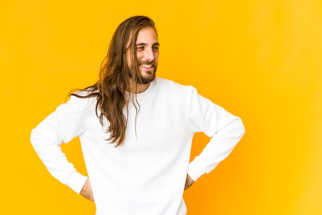 Junger mann mit langen haaren sieht glücklich aus und hat spaß daran, die hände auf dem bauch zu halten.