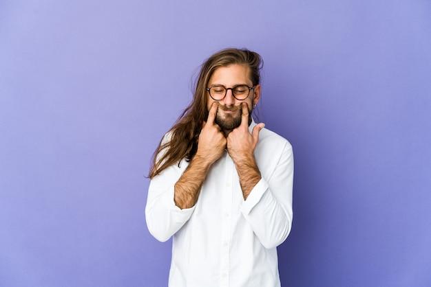 Junger mann mit langen haaren sieht zweifelhaft zwischen zwei optionen aus.