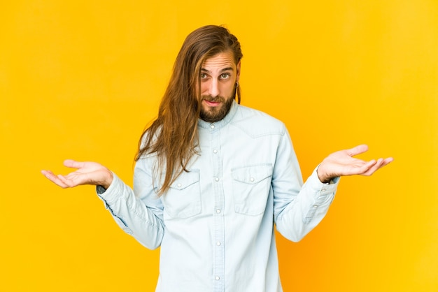 Junger mann mit langen haaren sieht zweifelnd aus und zuckt mit den schultern.