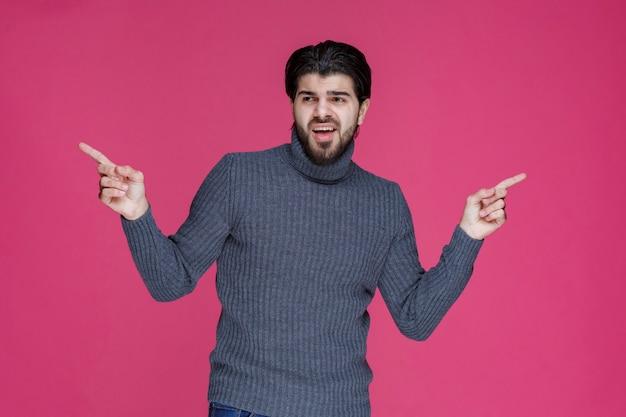 Junger mann mit langen haaren und bart, der etwas mit seinen fingern zeigt oder auf etwas zeigt.