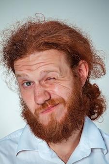 Junger mann mit langen roten haaren, die kamera mit verdacht betrachten