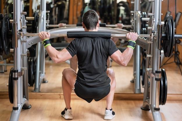 Junger mann mit langhantel kniebeugen im fitnessstudio zu tun.