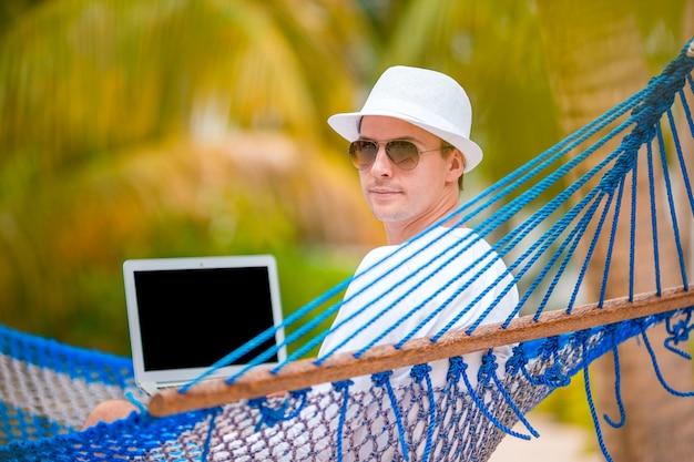 Junger mann mit laptop an der hängematte im tropischen urlaub