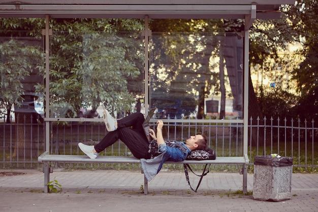 Junger mann mit laptop auf den knien liegt auf der öffentlichen verkehrsstation, während auf bus wartet.