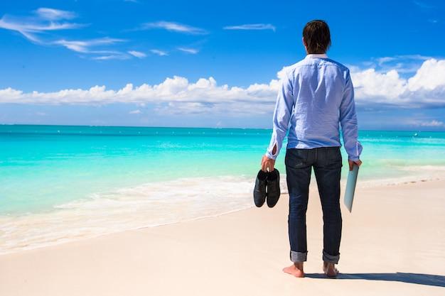 Junger mann mit laptop auf türkisozean am tropischen strand