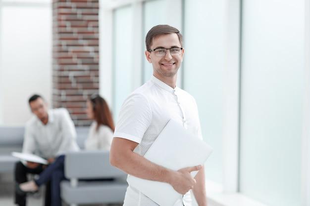 Junger mann mit laptop, der im büro steht. menschen und technologie