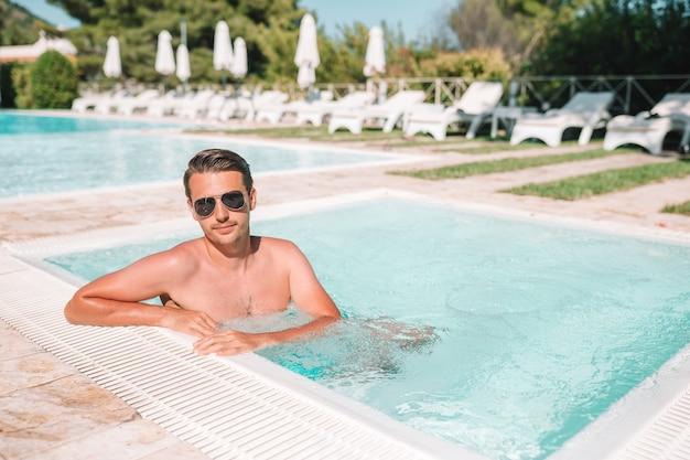 Junger mann mit laptop im außenschwimmbad.