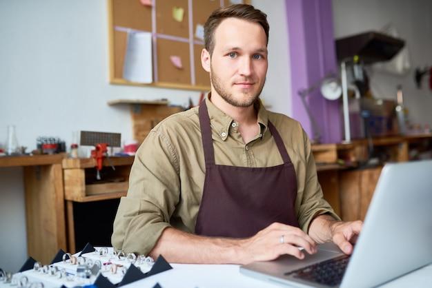 Junger mann mit laptop in schmuckwerkstatt