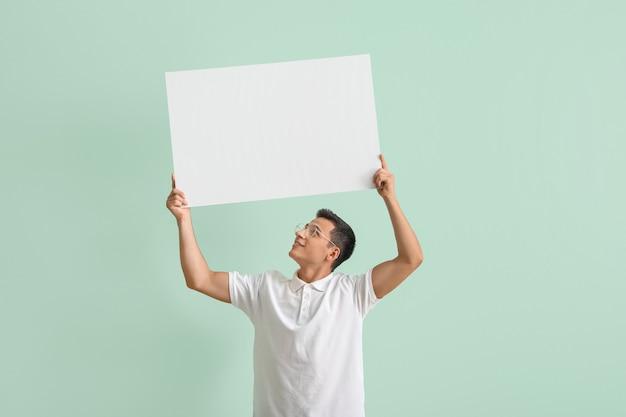 Junger mann mit leerem plakat auf grün