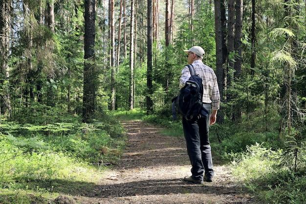 Junger mann mit leichtem rucksack geht langsam durch den wald