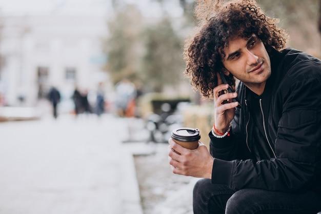 Junger mann mit lockigem haar, der kaffee trinkt und telefoniert
