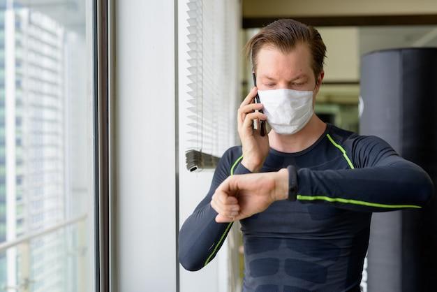 Junger mann mit maske, die am telefon spricht und smartwatch überprüft, die bereit ist, während covid-19 zu trainieren
