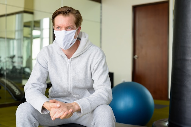 Junger mann mit maske, die an die turnhalle denkt und sitzt
