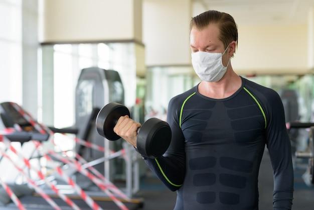Junger mann mit maske, die mit hantel im fitnessstudio während coronavirus covid-19 trainiert