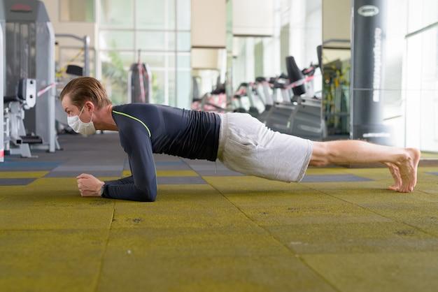 Junger mann mit maske, die plankenposition auf dem boden im fitnessstudio während coronavirus covid-19 tut