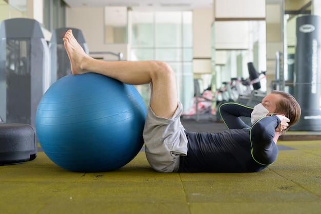 Junger mann mit maske, die sit-ups mit übungsball im fitnessstudio während coronavirus covid-19 tut