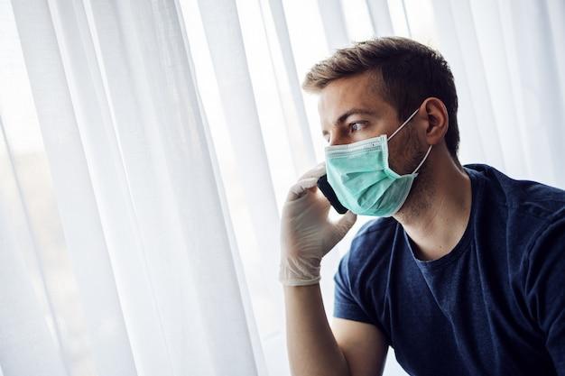 Junger mann mit maske und handschuhen, die handy tippend betrachten und besorgt schauen. bleib zu hause, weltpandemie. quarantäne.