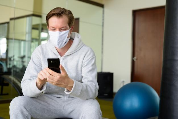 Junger mann mit maske unter verwendung des telefons und des sitzens im fitnessstudio