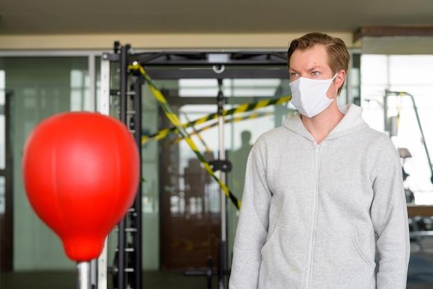 Junger mann mit maskendenken und bereit zum boxen im fitnessstudio