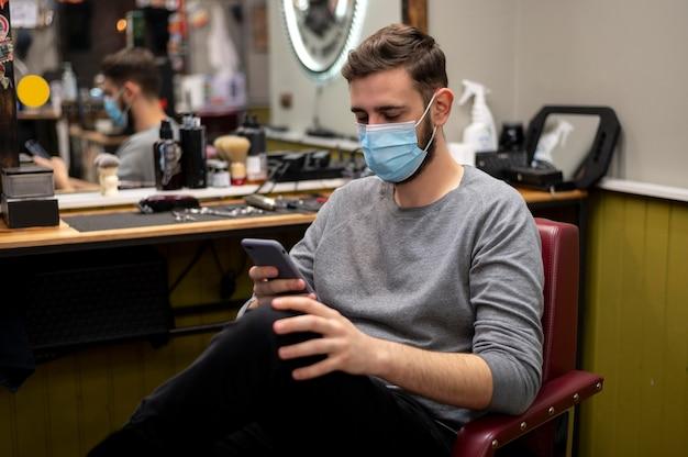 Junger mann mit medizinischer maske am friseurladen, der sein telefon überprüft