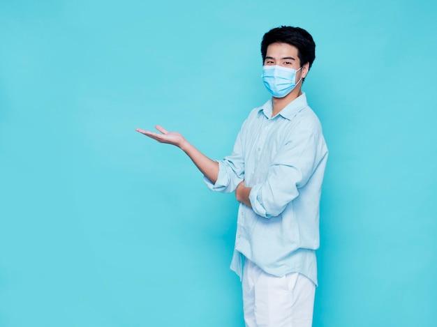 Junger mann mit medizinischer maske auf blauer wand, raum für text. konzept covid 19