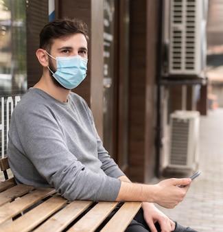 Junger mann mit medizinischer maske im freien