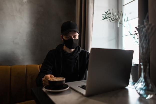 Junger mann mit medizinischer schutzmaske und schwarzer mütze in einem hoodie trinkt kaffee und sieht sich einen laptop in einem café an