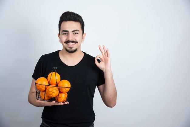 Junger mann mit metallischem korb voll von orangenfrüchten, die ok zeichen tun.