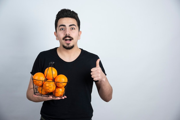 Junger mann mit metallischem korb voller orange früchte, die daumen oben zeigen.