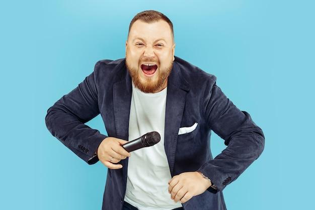 Junger mann mit mikrofon auf blauem, führendem konzept