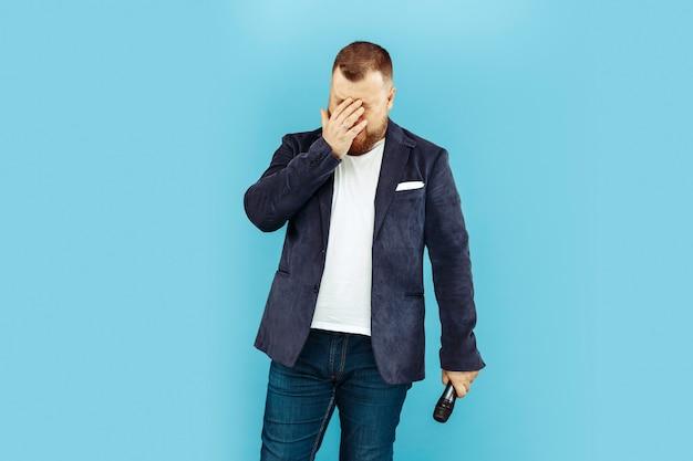 Junger mann mit mikrofon auf blauem hintergrund, führendes konzept