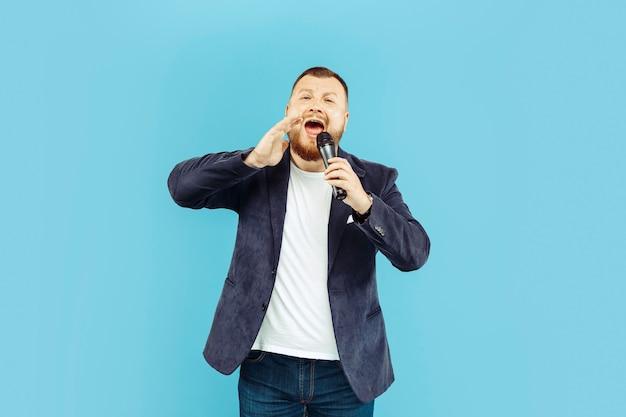 Junger mann mit mikrofon auf blauem raum, führendes konzept