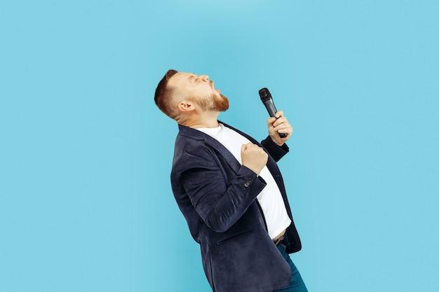 Junger mann mit mikrofon auf blauer wand