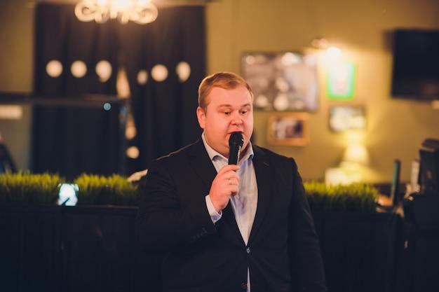 Junger mann mit mikrofon auf grauem hintergrund, führend mit mikrofon am studiokonzept. konzepte menschlicher emotionen und gesichtsausdrücke.