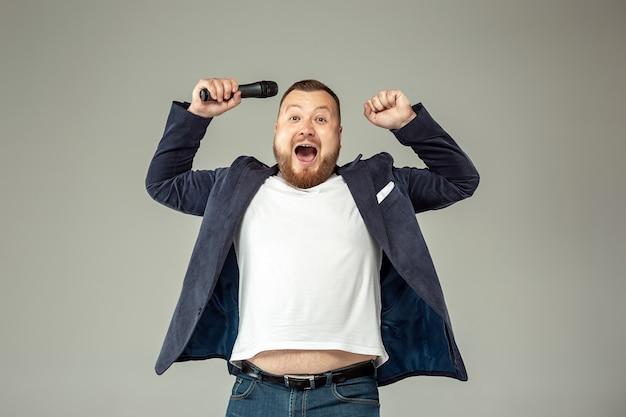 Junger mann mit mikrofon auf grauer wand, führend mit mikrofon