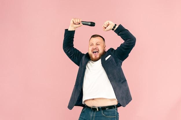 Junger mann mit mikrofon auf rosa, führend mit mikrofon