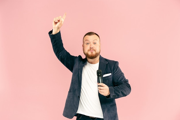 Junger mann mit mikrofon auf rosa hintergrund, führend mit mikrofon