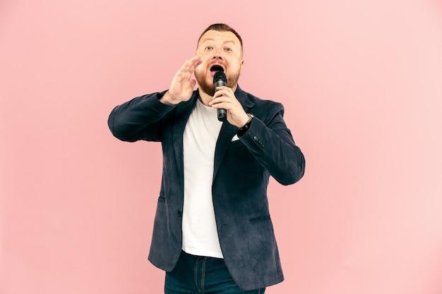 Junger mann mit mikrofon auf rosa wand, führend mit mikrofon