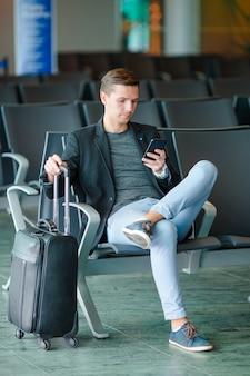 Junger mann mit mobiltelefon am flughafen beim warten auf einstieg.